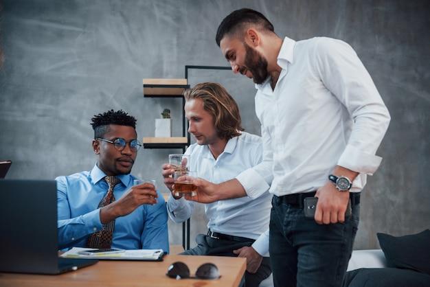 Beber whisky grupo de trabajadores de oficina multirraciales en ropa formal hablando sobre tareas y planes
