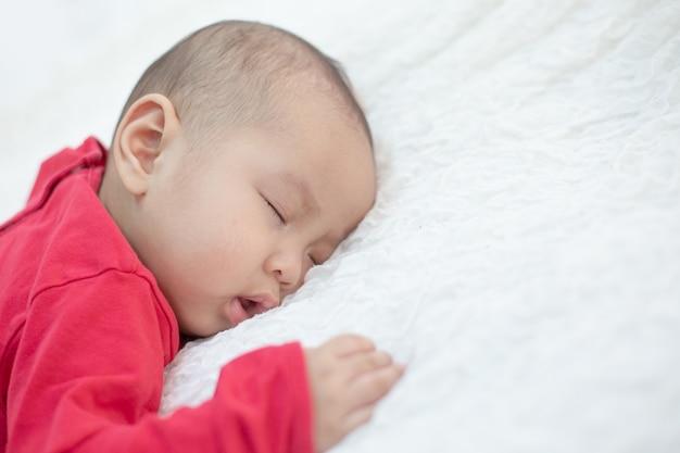 Bebés vestidos con camisas rojas durmiendo en la cama