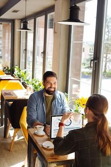 Bebida agradable. hombres agradables alegres hablando entre sí mientras beben café juntos