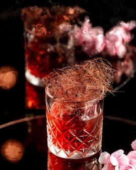 Bebida de alcohol rojo con decoración de pelos de maíz y flores.