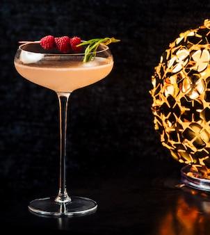 Bebida alcohólica adornada con rapberries en vaso de tallo largo