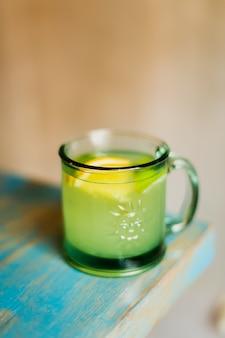 Bebida alcohólica caliente con menta y limón en una taza de vidrio
