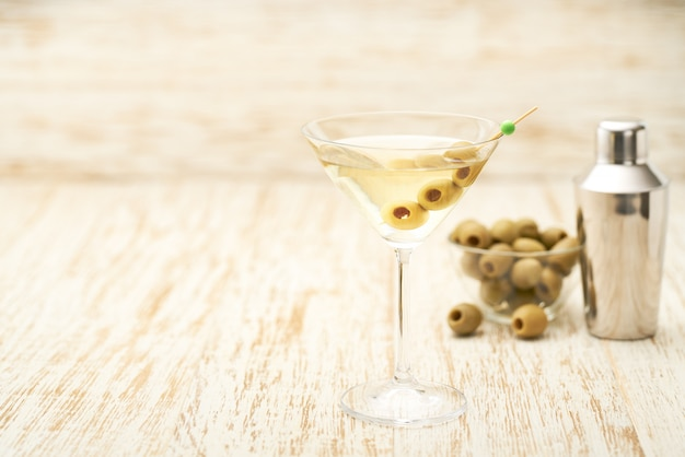 Bebida alcohólica cóctel con aceitunas verdes en mesa de madera