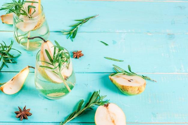 Bebida alcohólica cóctel de pera dulce con ron, licor, anís y romero sobre fondo de mesa de madera azul claro