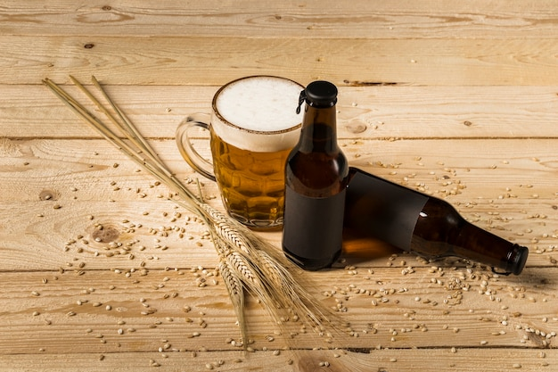 Bebida alcohólica y espigas de trigo en superficie de madera.