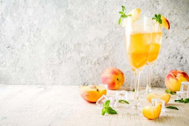 Bebida alcohólica fría de verano, cóctel bellini de durazno helado con hojas de menta, fondo de hormigón ligero