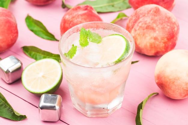 Bebida alcohólica fría de verano, cóctel bellini de durazno helado con hojas de menta,