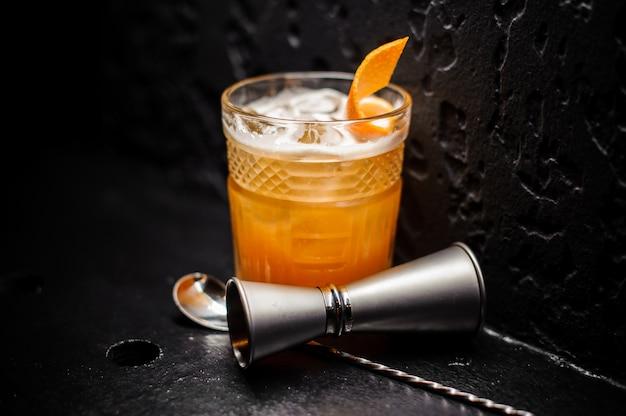Bebida alcohólica de naranja fresca con hielo y piel de naranja