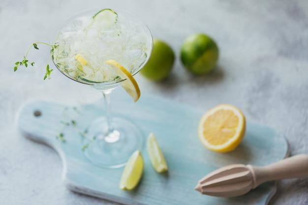 Bebida alcohólica de verano. cóctel refrescante casero con ginebra, vodka o tequila, pepino, lima, cubitos de hielo y tomillo