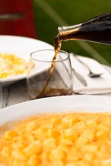 Bebida alcohólica vertiendo en vidrio con sabrosa pasta italiana en la mesa