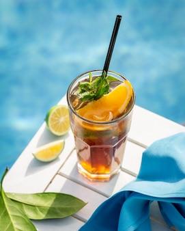 Bebida amarilla con hojas de naranja, limón y menta junto a la piscina.