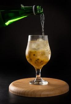Bebida brasileña, sake caipirinha con maracuyá en un recipiente, sobre la superficie de madera redonda oscura