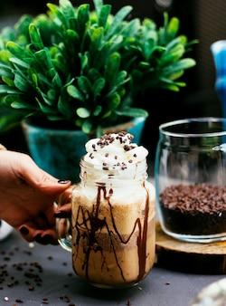 Bebida de café con crema batida y granos de café.