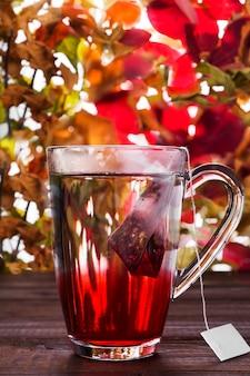 Bebida caliente con bolsita de té de hibisco rojo en vaso