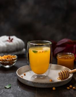 Bebida caliente casera con espino amarillo y miel en un vaso