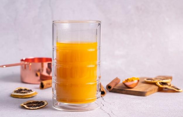 Una bebida caliente de cúrcuma, leche dorada. especia natural saludable, en un vaso termo alto