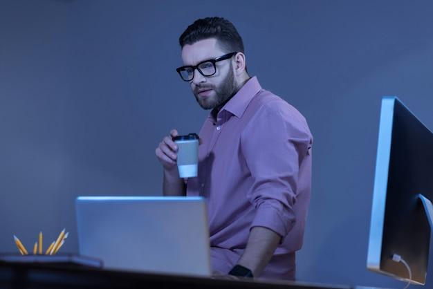 Bebida caliente. grave hombre agradable guapo sosteniendo una taza de café y mirando la pantalla del portátil mientras está sentado en la mesa