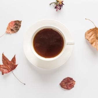 Bebida caliente con hojas secas sobre superficie blanca.