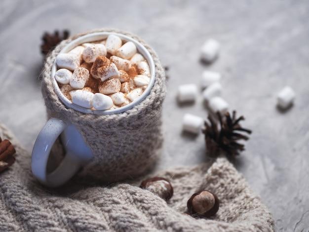 Bebida caliente de invierno chocolate, cacao o café con malvaviscos sobre la mesa en una taza tejida con canela