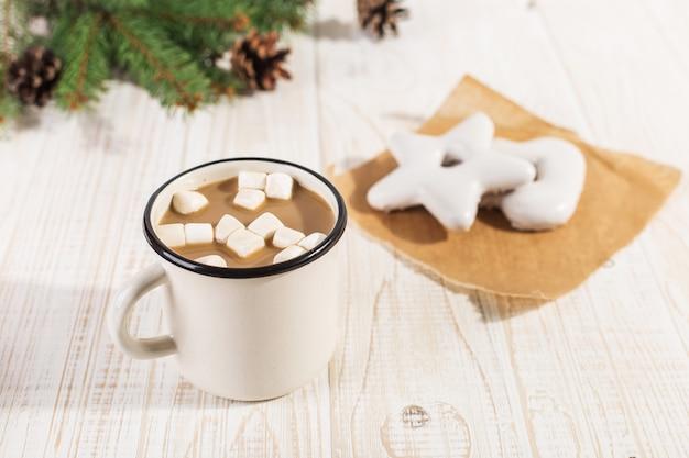 Bebida caliente de navidad con malvaviscos en una taza de hierro y galletas de jengibre, sobre una mesa blanca.