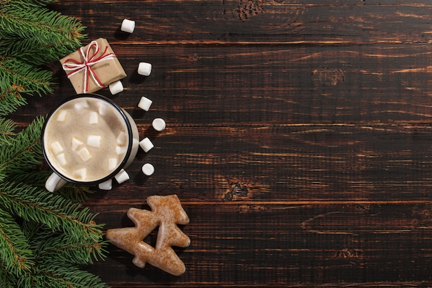 Bebida caliente de navidad con malvaviscos en taza de hierro y galletas de jengibre, sobre una mesa de madera. , vacaciones, tarjeta de felicitación copyspace.