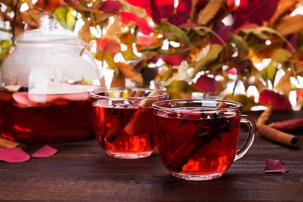 Bebida caliente con té rojo de hibisco con manzana, canela y anís en tetera de vidrio y dos vasos.