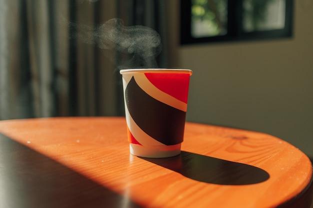 Bebida caliente en un vaso de papel sobre la mesa con la cálida luz de la mañana.