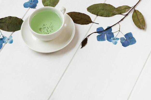 Bebida caliente verde natural con rosas y plantas en escritorio
