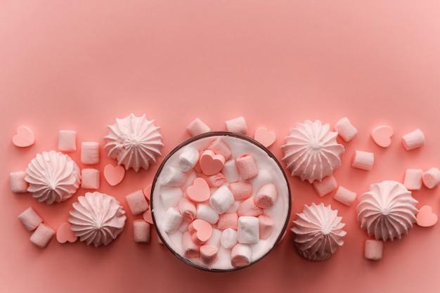 Bebida caliente vista superior con crema batida, malvaviscos y caramelos de chocolate en forma de corazón entonado