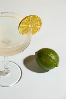 Bebida casera clásica margarita con limón y sal sobre fondo blanco.