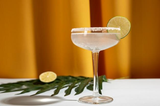 Bebida casera de margarita con lima y hoja de palma en la mesa contra la cortina amarilla