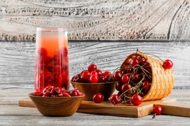 Bebida de cereza en una jarra con cerezas, mermelada vista lateral en madera y tabla de cortar