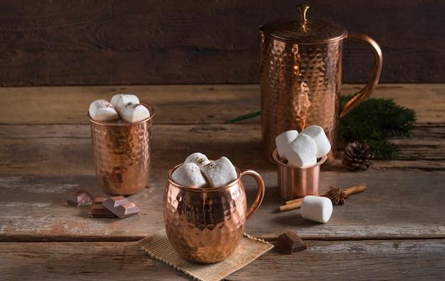 Bebida de chocolate o cacao caliente cubierta con malvaviscos en tazas de cobre