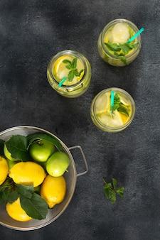 Bebida cítrica de verano. limonada fresca sin azúcar con manzanas y limón en una vista superior oscura