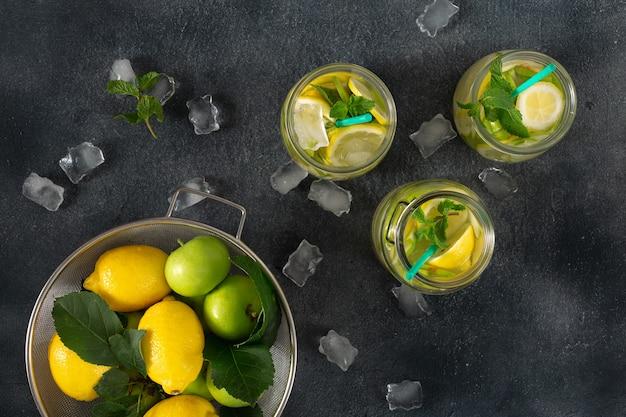 Bebida cítrica de verano. limonada fresca con manzanas y limón en una vista superior oscura