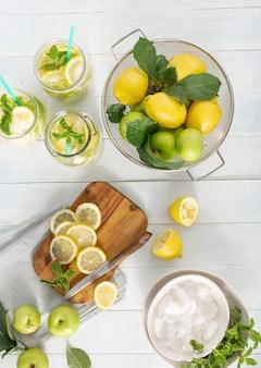 Bebida de cítricos. limonada fresca con manzanas y limón en la vista superior de la mesa de madera
