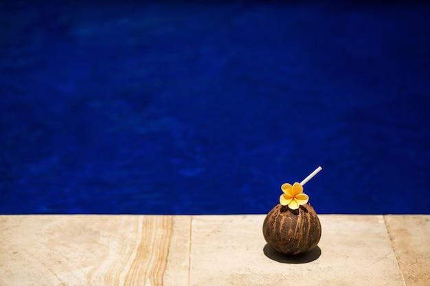 Bebida de coco tropical con flor amarilla, en el borde de la piscina. hotel relajante