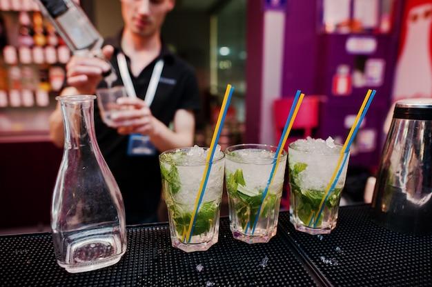 Bebida de cóctel de tres mojitos con tubos de colores y fondo de jarra barman en el bar