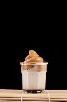 Bebida coreana café dalgona en vaso. leche fría con espuma de café instantáneo. orientación vertical, espacio de copia.