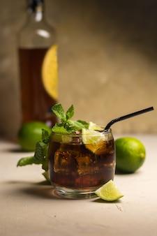 Bebida cuba libre con hojas de menta y trozos de lima. bebida alcohólica con ron y cola.