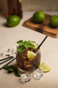 Bebida cuba libre con hojas de menta y trozos de lima.