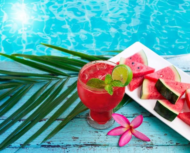 Bebida de sandía en vasos con rodajas de sandía cerca de la piscina de agua