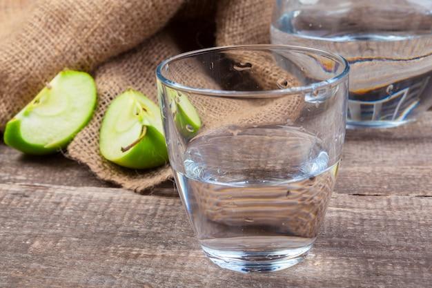 Bebida de desintoxicación dietética con rodajas de manzana en agua limpia y una manzana fresca en una mesa de madera, de cerca
