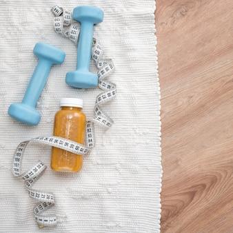 Bebida de desintoxicación con pesas y cinta métrica