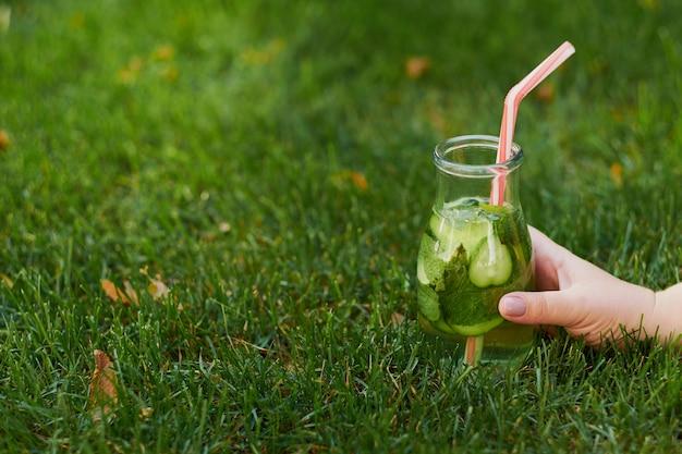 Bebida de desintoxicación verde saludable en la hierba de verano en la mano. tarro de té frío fresco al aire libre.