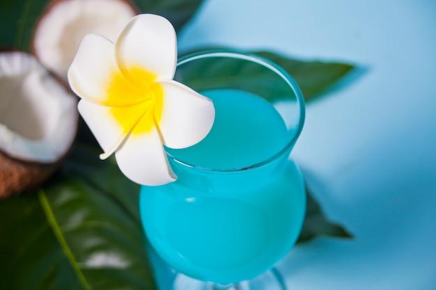 Bebida exótica tropical azul curacao cóctel en un vaso con flor de frangipani plumeria, hoja de palma, coco fresco en el fondo.