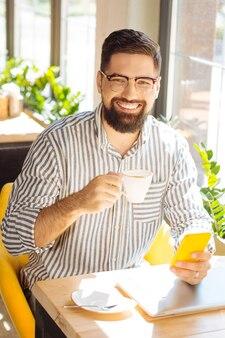 Bebida favorita. hombre barbudo alegre sosteniendo su teléfono inteligente mientras toma su café de la mañana en la cafetería
