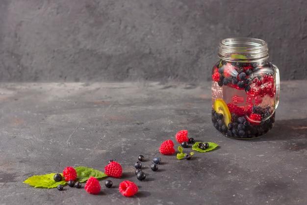 Bebida fresca de desintoxicación con frambuesas, arándanos y kiwi en mason jar mug. limonada en un vaso con una menta. el concepto de nutrición adecuada y alimentación saludable. dieta de fitness. copiar espacio para tex