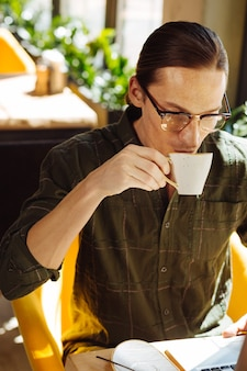 Bebida fresca. hombre guapo agradable sosteniendo una taza mientras toma un sorbo de café