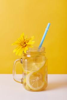 Bebida fresca con limón, vidrio decorado con flor amarilla.